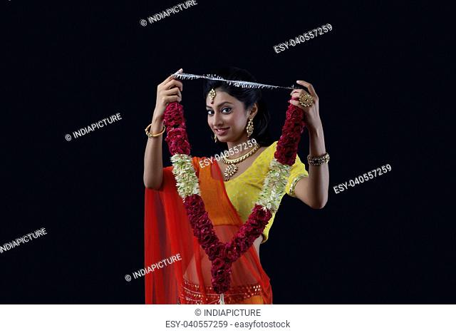 Portrait of a beautiful bride holding a garland
