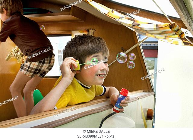 Two boys blowing bubbles out of caravan