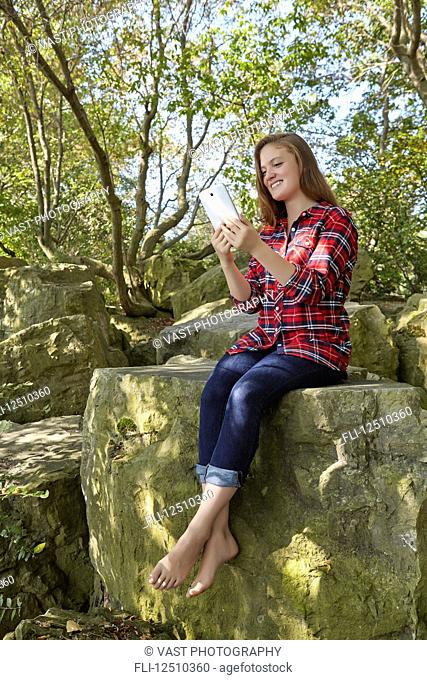 A teenage girl wearing jeans and a plaid shirt in bare feet sits on a boulder using her smart phone, Woodbine Beach; Toronto, Ontario, Canada