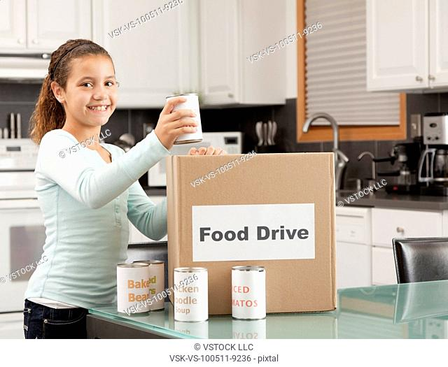 USA, Illinois, Metamora, Portrait of smiling girl (10-11) putting canned food into cardboard box in kitchen