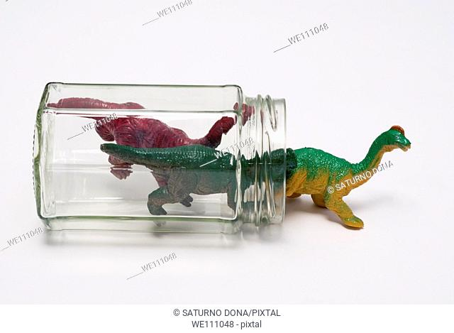 plastic dinosaurs getting out of glass jar