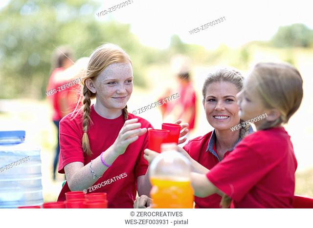 South Africa, Kids on field trip pouring refreshment drinks