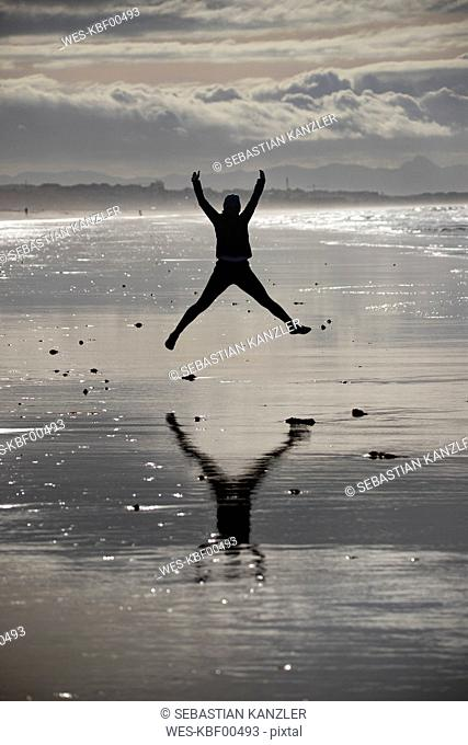 Female jogger jumping at the beach
