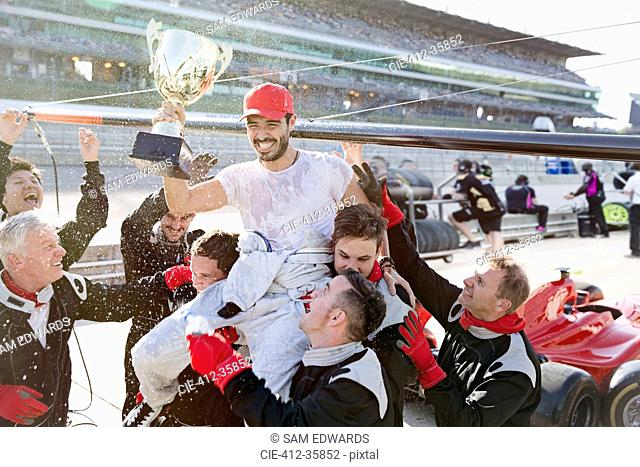 Formula one racing team carrying driver with trophy on shoulders, celebrating victory on sports track