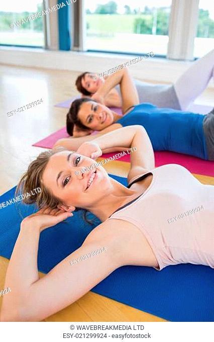 Women on mats doing sit ups in fitness studio