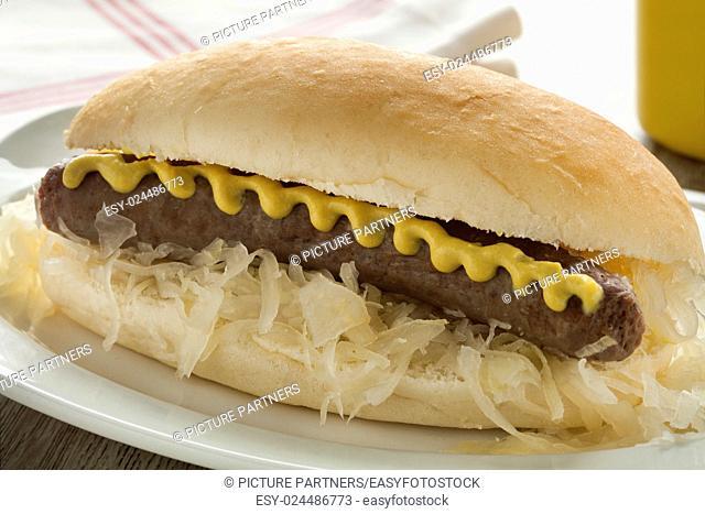 White bun with sauerkraut, sausage and mustard close up