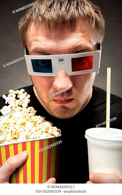 Funny man watching 3D movie, drinking soda and eating popcorn