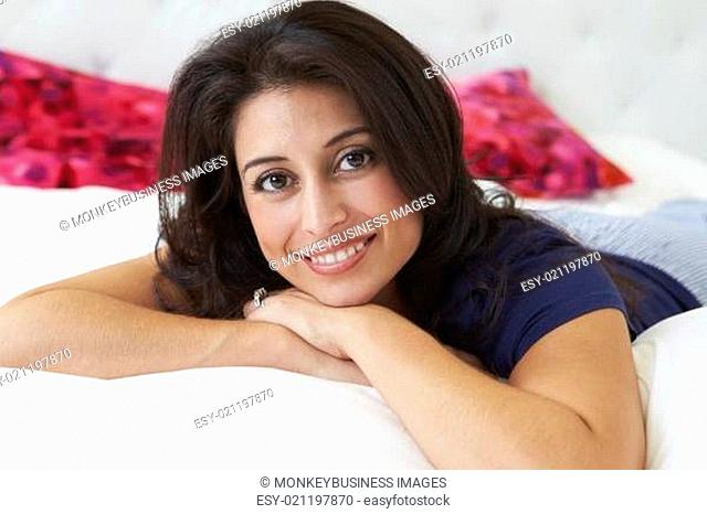 Woman Relaxing In Bed Wearing Pajamas