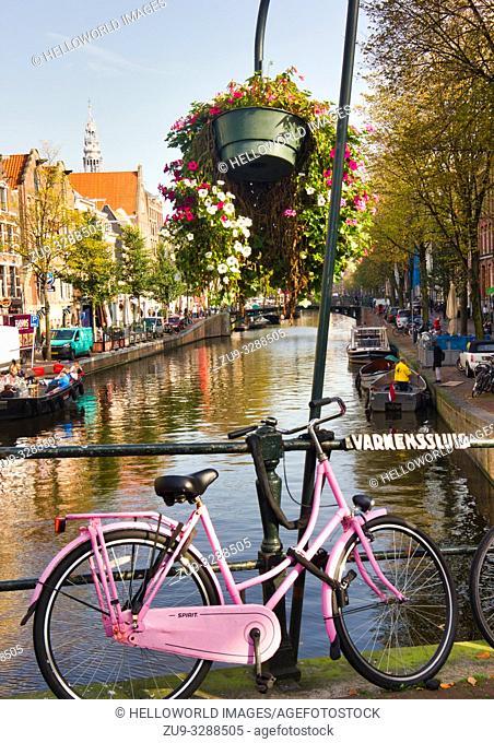 Pink sit up and beg bicycle on Varkenssluis above the Oudezijds Voorburgwal Canal, Amsterdam, Holland, Europe. Varkenssluis (Varkens lock or Pig lock) is a...