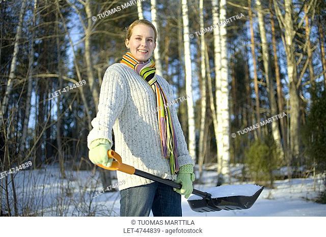 Woman shoveling snow on cottage yard