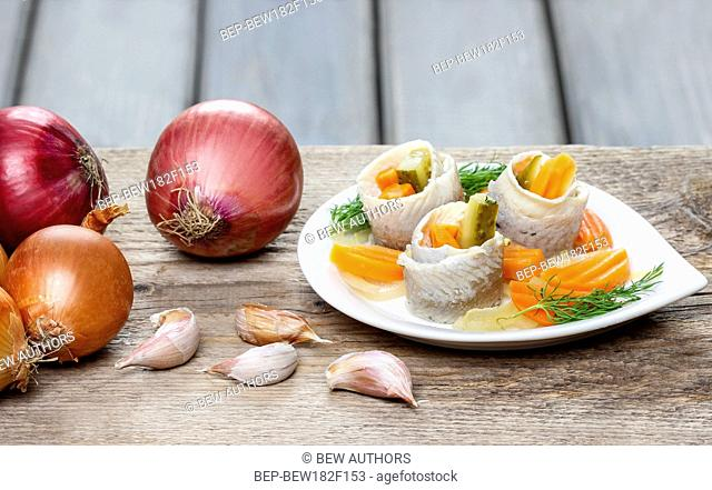 Pickled herring rolls with vegetables on brown wooden background. Fresh onions and garlic, copy space