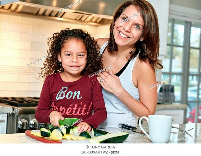 Mother helping daughter chop vegetables in kitchen, looking at camera smiling