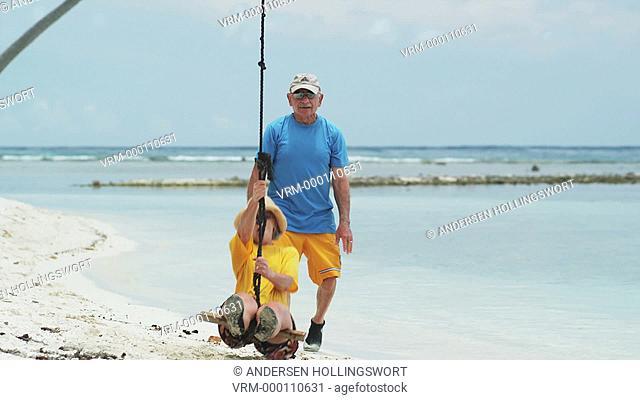 senior couple swinging on the beach