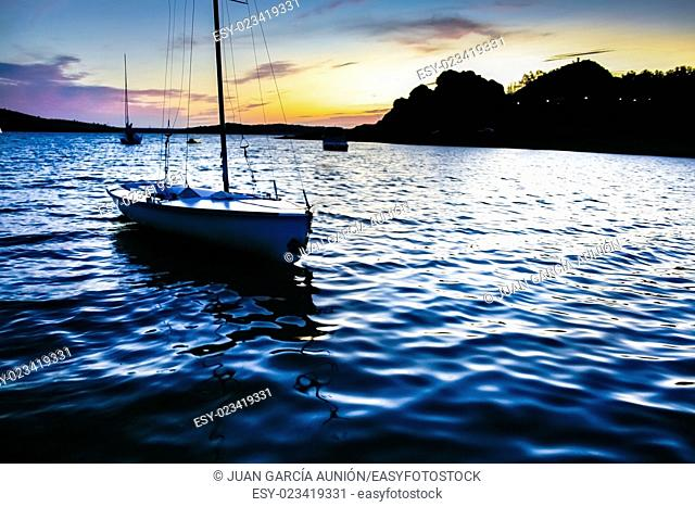 Sailboats beside the shore of Alange Reservoir at dusk, Extremadura, Spain