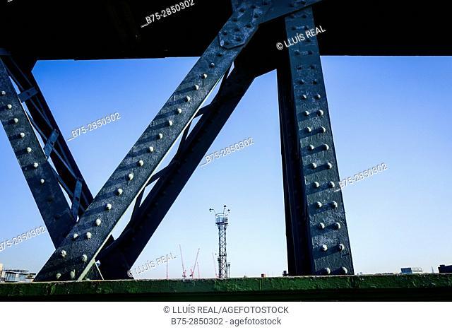 Vista de una torre metalica y gruas a traves de una estructura de hierro de un puente.Hampstead Village, London UK, Europa