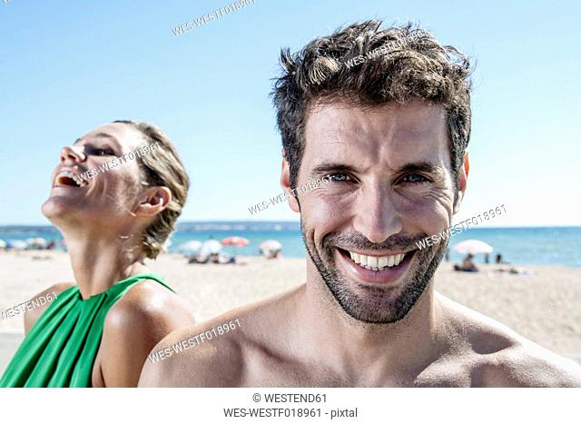 Spain, Mid adult couple sitting at beach, smiling