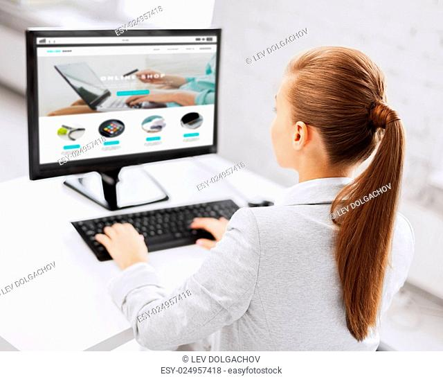 business, people, technology, internet shopping and education concept - businesswoman or student girl with online shop on computer screen sitting at office...