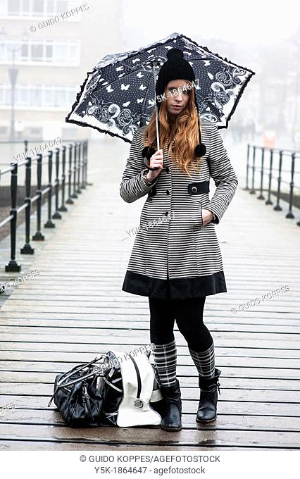 Breda, Netherlands. Young, fashionable and redheaded woman, standing on a vintage bridge