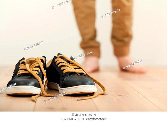 Pair of clean lace up sneakers on a wooden floor with the blurred legs of a barefoot boy in the background