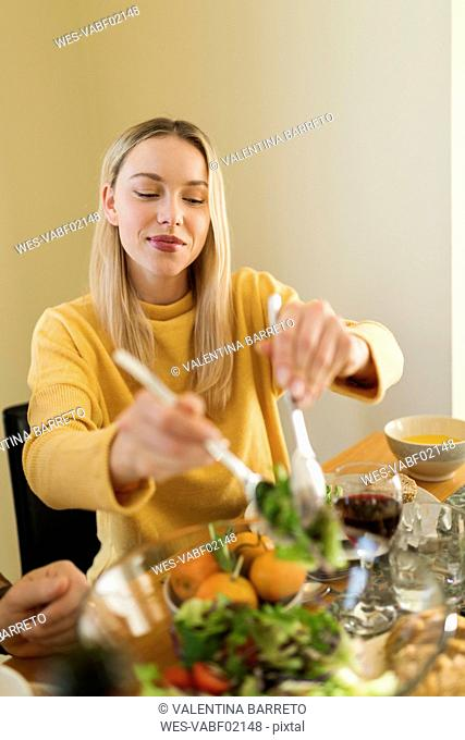 Young woman eating salad at a lunch with friends