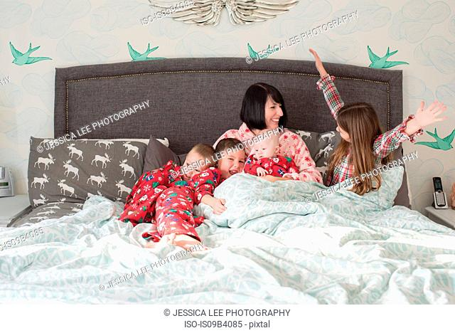 Mother and children lying in bed together