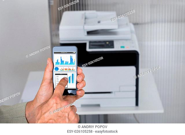 Cropped image of businessman giving print command on smart phone in office