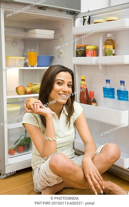 Woman holding an apple in front of a refrigerator