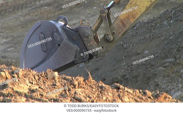 Closeup of crawler mounted backhoe bucket digging on construction site