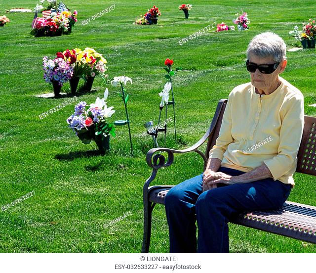 An elderly woman sitting on a bench at a cemetery grieving