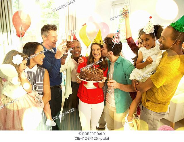 Multi-ethnic multi-generation family celebrating birthday with chocolate cake