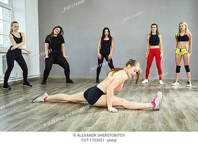 Friends looking at young woman doing splits at dance studio