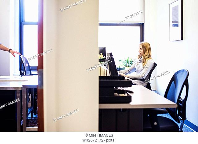 A shot of the doorway to two offices, a young woman sitting at a desk in one, and a man touching the back of a desk chair in the other