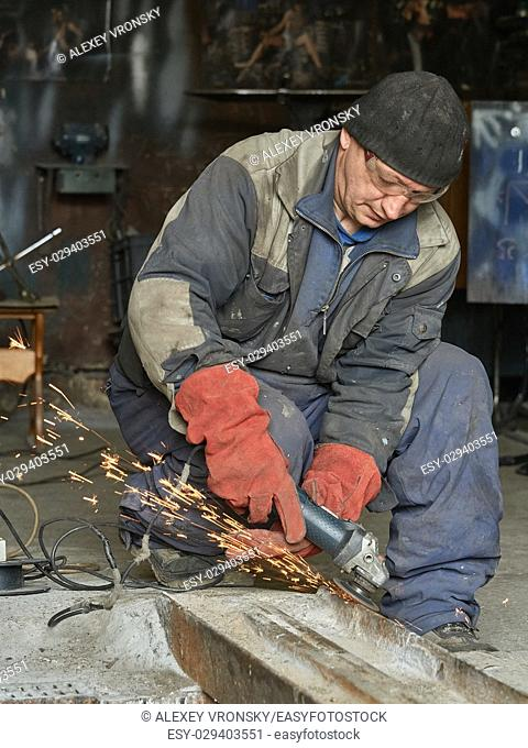 Worker grinds a metal rail for subsequent welding. The photo shows the sparks from the grinding wheel