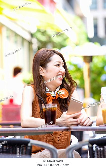 Business woman operating her smart phone at an outdoor cafe