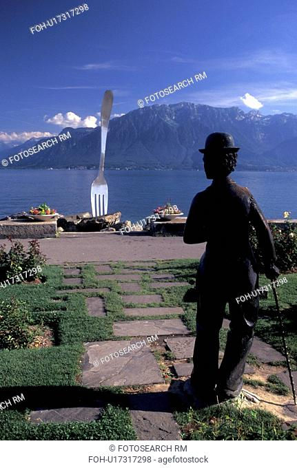 Charlie Chaplin, Vevey, Switzerland, Lake Geneva, Alps, Vaud, Charlie Chaplin statue and sculpture of a huge fork along the lakefront park along Lac Leman in...
