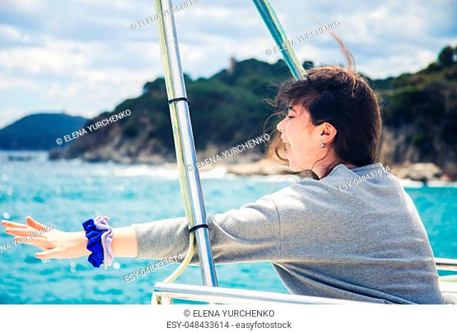 A teenage girl emotionally expresses her joy and enjoys a spring vacation in a sea voyage on a pleasure boat