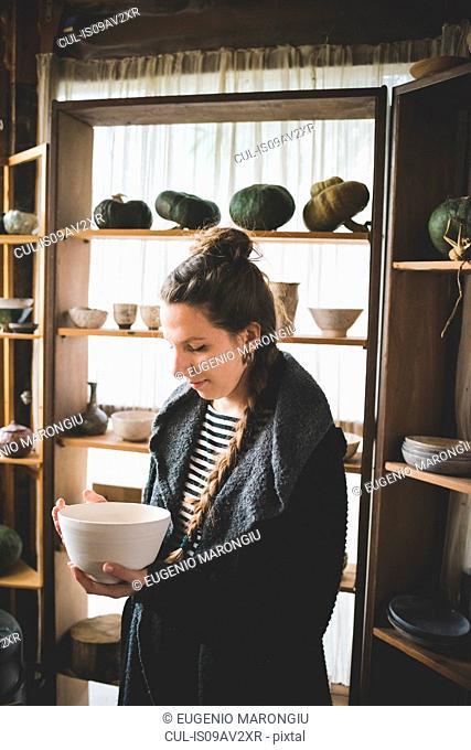 Young woman holding ceramic dish in front of shelves displaying clay pots and pumpkins