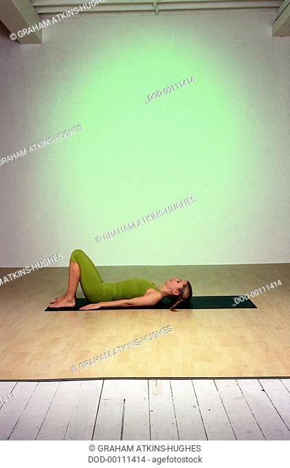 Stay Young, Full Shoulderstand, woman lying on back, on green mat, profile, knees bent, feet together, soles of feet flat on floor, arms by sides