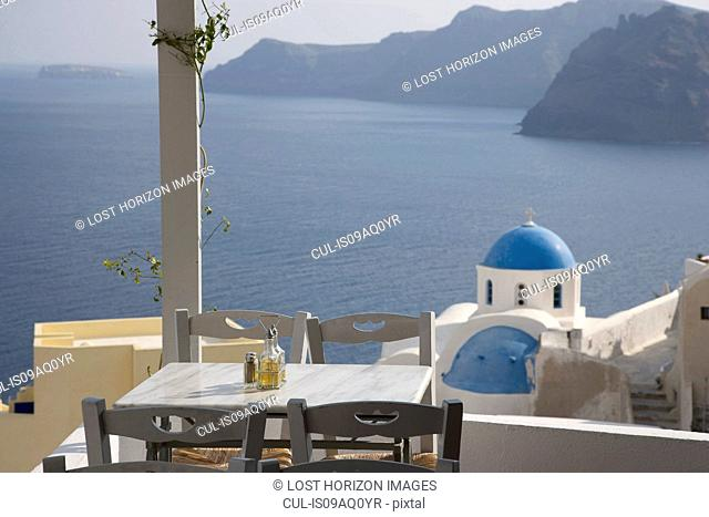 View of balcony restaurant and white washed church, Oia, Santorini, Cyclades, Greece