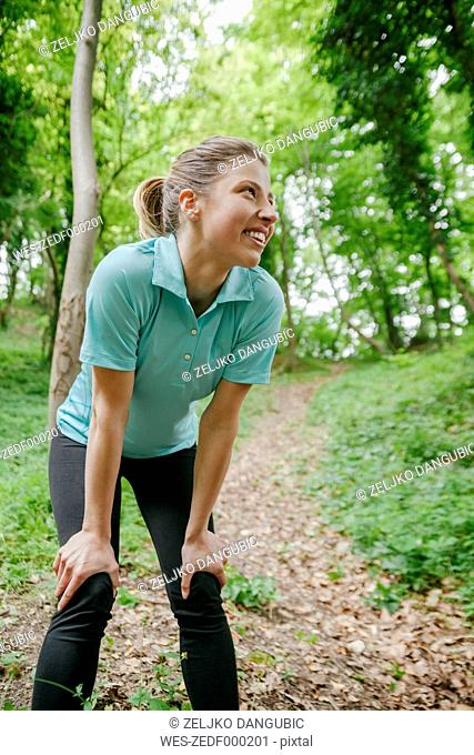 Smiling sportswoman resting in forest