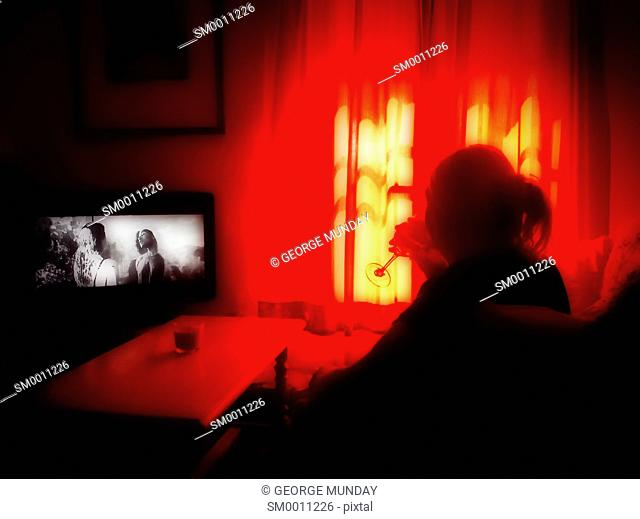 Woman watching television and drinking wine,