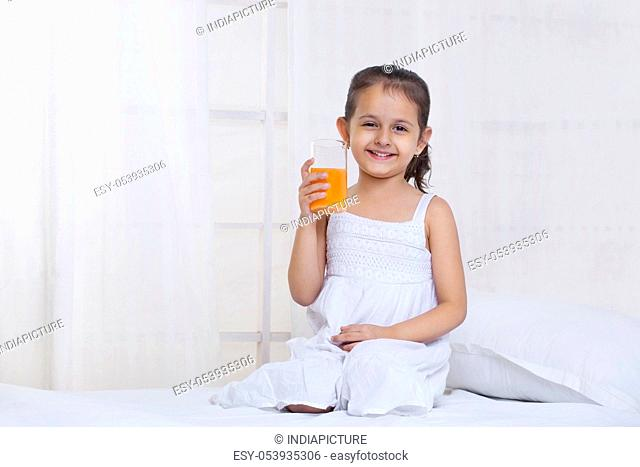 Cute little girl holding glass of juice