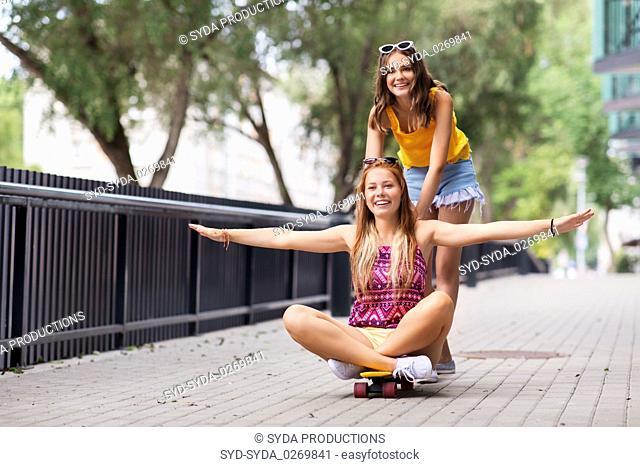 teenage girls riding skateboard on city street