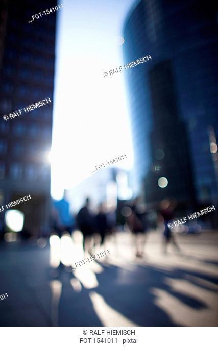 Defocused image of people walking on street amidst buildings in city