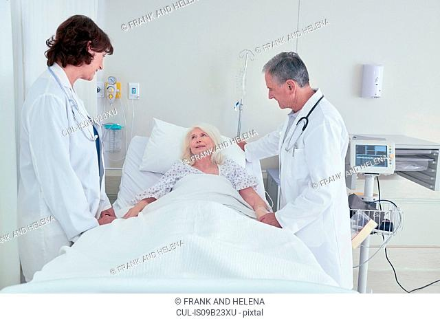 Two doctors talking to senior female patient in hospital bed