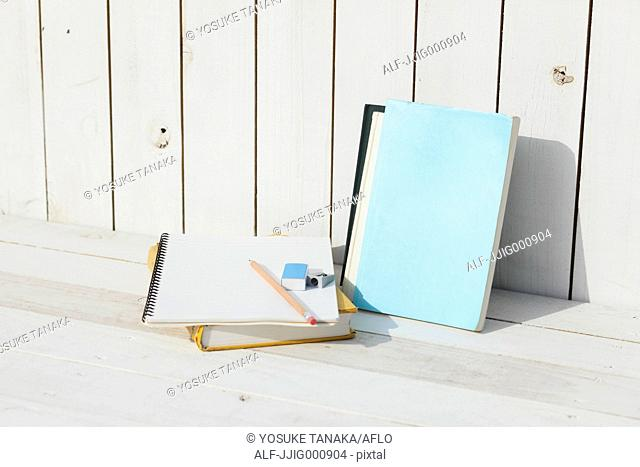 Pencil and notebooks against white wooden wall