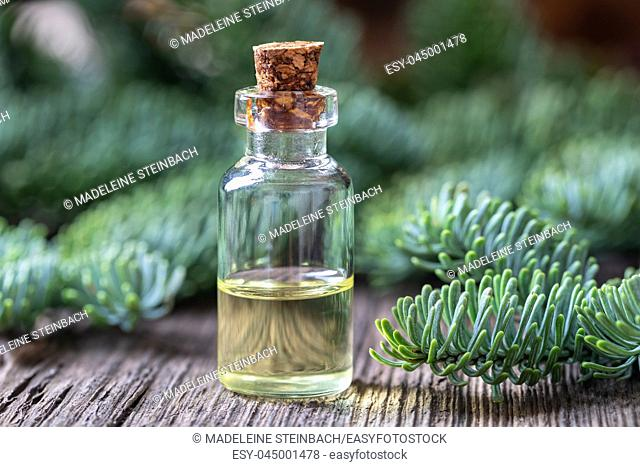 A bottle of essential oil with fir branches