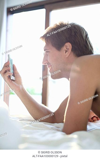 Man lying in bed using multimedia smartphone to video chat