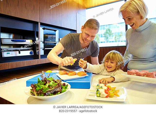Family in the kitchen. Three generations. Healthy eating. Healthy growth. Taking lemon fish