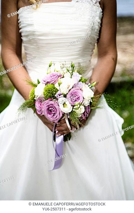 Hands of bride with bouquet of flowers